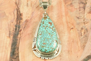 Genuine High Grade Kingman Web Turquoise set in Sterling Silver Pendant. Created by Navajo Artist Phillip Sanchez. Signed by the artist. The Mineral Park Mine, in the Cerbat Mountains 14 miles northwest of Kingman, was first mined by Indians centuries before white man came to the area. It is one of the three sites of prehistoric mining localities in the state of Arizona. Mineral Park was the most extensively worked area by the Indians of the three. S.A. Chuck Colbaugh found a cache of stone hammers uncovered in ancient trenches and tunnels, when he had the turquoise mining concession in May of 1962. Ithaca Peak and Turquoise Mine &#40;formally called Aztec Mountain or Aztec Peak&#41; are the most famous of the peaks in the area containing turquoise. Free 18&quot; Sterling Silver Chain with purchase of pendant.